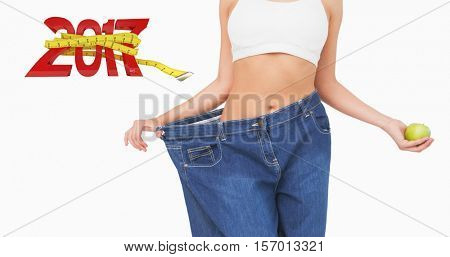 Mid section of slim woman wearing too big jeans holding an apple against new year with tape measure