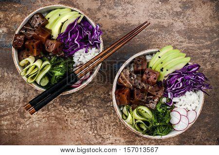Hawaiian tuna poke bowl with seaweed avocado red cabbage slaw radishes and black sesame seeds. Top view overhead flat lay