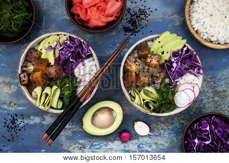 Hawaiian tuna poke bowl with seaweed avocado red cabbage slaw radishes and black sesame seeds. Top view overhead flat lay
