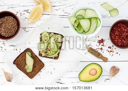 Holewheat toast with avocado guacamole and cucumber slices. Breakfast with spicy avocado sandwiches on whole grain bread. Vegetarian food healthy diet concept. Mexican cuisine. Overhead flat lay top view