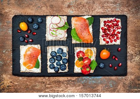 Bruschetta crostini appetizers mix set with various toppings. Variety of small sandwiches with salmon tomatoes ricotta blueberries and pomegranate seeds on crisp rye bread
