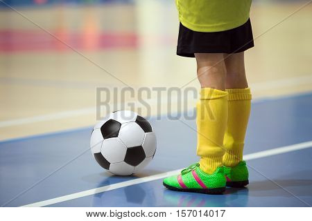 Football futbal training for children. Indoor soccer young player with a soccer ball in a sports hall. Player in yellow uniform. Sport background.