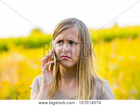 Horizontal photograph of upset woman calling on mobile phone for help because of pollen allergy outdoors.