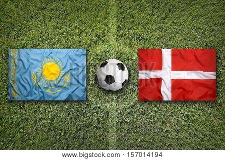 Kazakhstan vs. Denmark flags on a green soccer field, 3d rendering