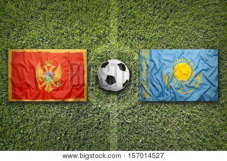 Montenegro vs. Kazakhstan flags on a green soccer field, 3d rendering