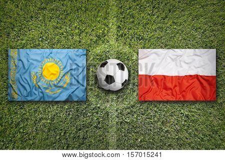 Kazakhstan vs. Poland flags on a green soccer field, 3d rendering