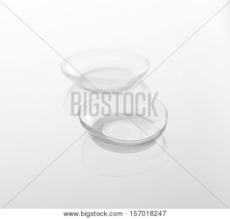 Pair of contact lenses on light background, close up view. Medicine and vision concept