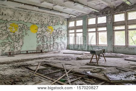ruined school gym with sports equipment remains and debris in Pripyat