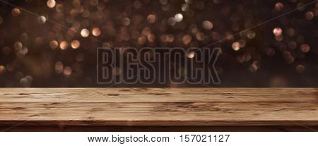 Gold shimmering panorama for public holidays in front of a wooden table and a concept poster