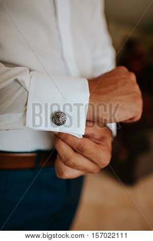 Man putting on cuff-links as he gets dressed in formal wear