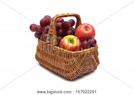 grapes and apples in a basket on a white background. horizontal photo.