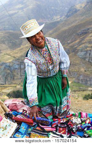 PERU - SEPTEMBER 6, 2015: Unidentified woman selling the traditional local textile items on the La Raya Pass near Sicuani, Peru