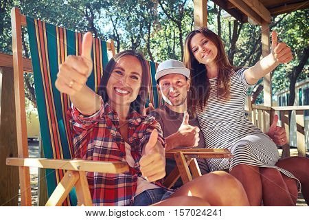 Low angle side shot of 3 people showing thumbs up while sitting on comfortable summer beach chairs at a resting house