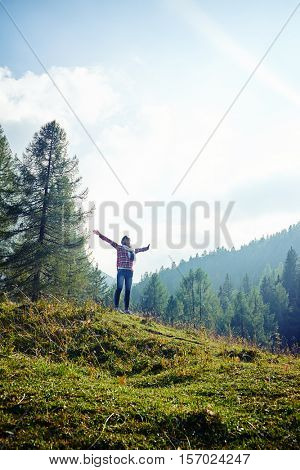 Mid low angle shot of positive woman who is spreading hands and feeling the freedom on the mountain peak on a fair day. Stunning vista of the mountain valley covered with majestic forests