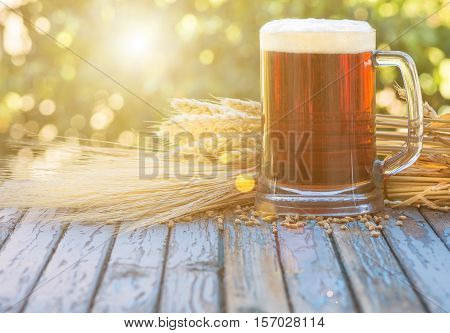 large glass of dark beer malt hops barley ears standing on an old wooden table dyeing natural background