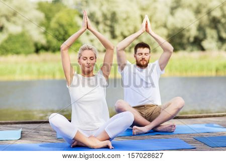 fitness, sport, yoga and healthy lifestyle concept - people meditating in lotus pose on river or lake berth