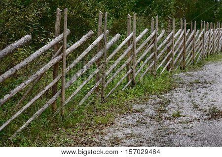 slanting fence made of poles in rural