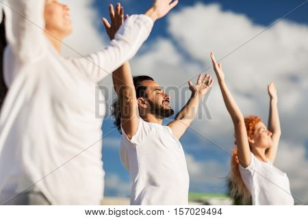 fitness, sport, and healthy lifestyle concept - group of people making yoga exercises outdoors