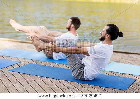 fitness, sport, yoga, people and healthy lifestyle concept - men making half-boat pose on mat outdoors on river or lake berth