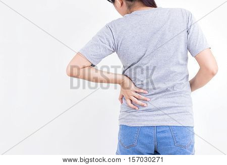 Portrait of young woman touching her back with pained expression suffering from backache after long working hours Healthy concept.