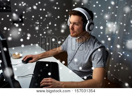 technology, gaming, entertainment, let's play and people concept - young man in headset with pc computer playing game at home and streaming playthrough or walkthrough video over snow