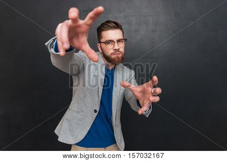 Concentrated bearded young businessman in glasses standing with hands outstretched to camera