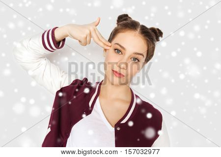 winter, christmas, people, stress and gesture concept - bored teenage girl making headshot by finger gun gesture over gray background and snow