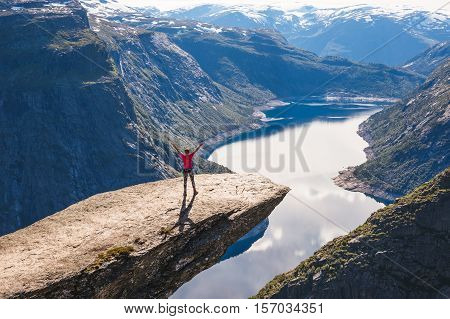 Young woman relaxon Trolltunga. Happy girl enjoy beautiful lake and good weather in Norway