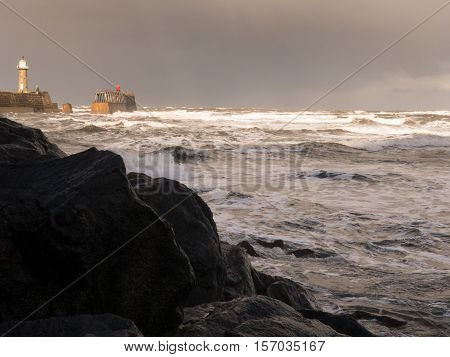 WHITBY ENGLAND - NOVEMBER 5: East Lighthouse and rough sea crashing against rocks. In Whitby North Yorkshire England. On 5th November 2016.