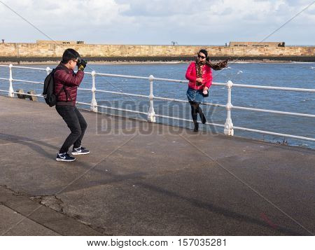 WHITBY ENGLAND - NOVEMBER 5: Oriental tourist taking photo of woman in high wind Whitby. In Whitby North Yorkshire England. On 5th November 2016.