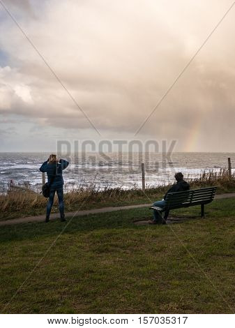 WHITBY ENGLAND - NOVEMBER 5: Man and woman admire rainbow Whitby clifftop. In Whitby North Yorkshire England. On 5th November 2016.