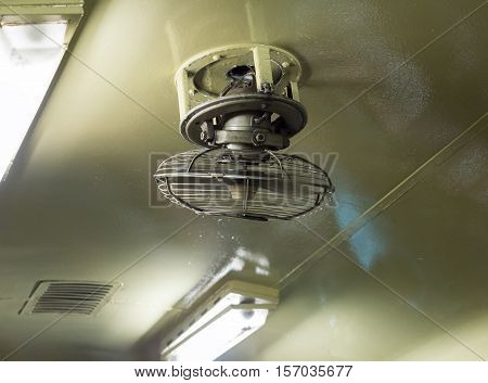 Old orbit fan with the electrical bulb on the ceiling of the train.