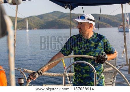 Man skipper steers sailing boat on the Sea. Luxury yacht.