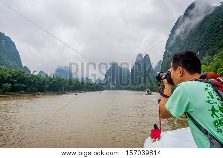 Photographer Taking Pictures On Li River Cruise, China