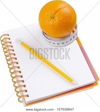 Orange with tape measurer around it on top of a food journal - diet concept