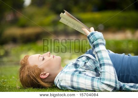 Young woman sitting outside reading