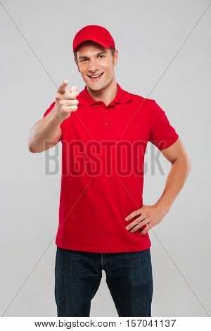 Smiling deliveryman. looking at camera. isolated gray background