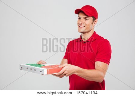 Side view of pizza delivery man. in studio. isolated gray background