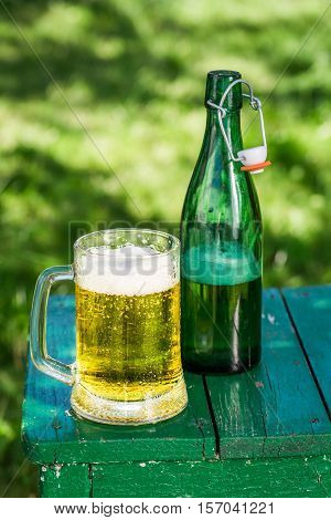Cold Beer In Garden On Old Wooden Table