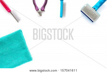 Cat and dog grooming tools: fine toothed comb wide toothed comb slicker brush small nail clipper and a microfiber towel isolated on white background.
