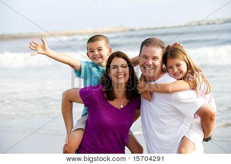 Boldog, szerető család játszik a tengerparton