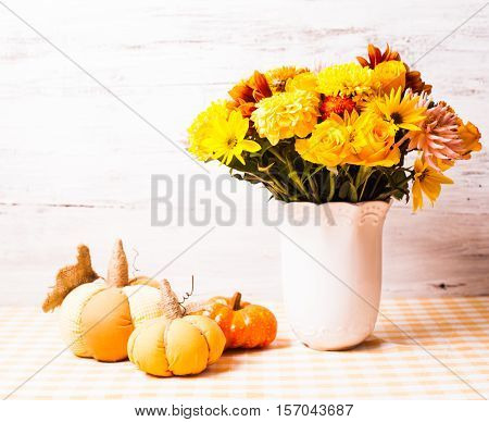 Vase with flowers and small orange textile pumpkins on a table