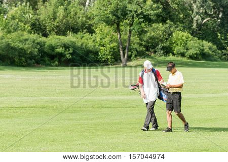 Golfer And Caddy On A Golf Course