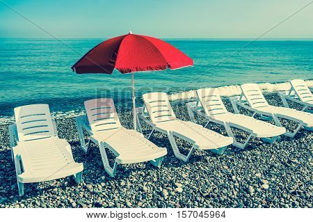 Sunbathing plastic beds and red umbrella on the beach near sea - retro style