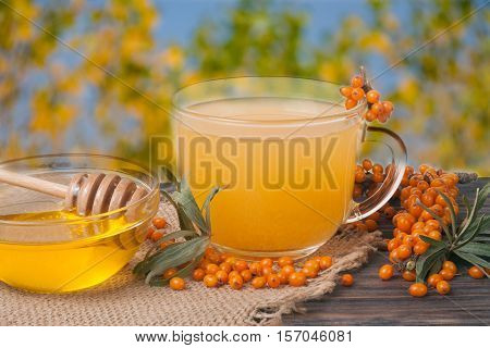 Tea of sea-buckthorn berries on sackcloth and wooden table with blurred garden background.