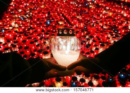 Two hands holding a lampion at cemetery with a large group of lampions lined up beneath the cross on All Saints day in Croatia.