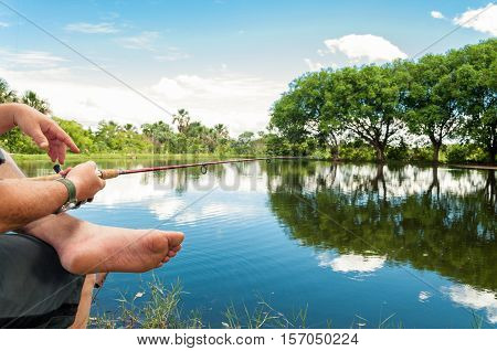 Man fishing holding a rod on a lake with a beautiful nature around. Lake with reflection of trees on the water.