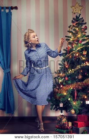 portrait of nice young woman hanging around christmas tree on x-mas  eve