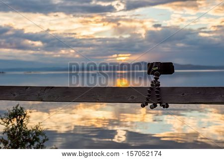 Smartphone attached on flexible tripod facing the sea at sunset