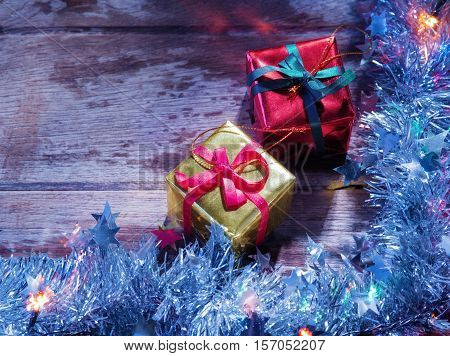 close up view of christmas tree garland, gifts  and lights on wooden back
